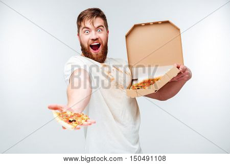 Cheerful bearded man giving slice of pizza isolated on white background