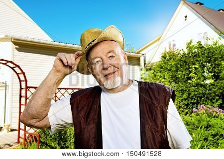 Portrait of a happy senior man standing in his garden on a sunny summer day. Gardening and vegetable farming.