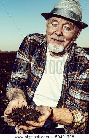 An elderly farmer holds a handful of fertile black soil in his hands and smiling. Agriculture, crop concept.
