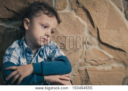 sad little boy sitting near the wall at the day time