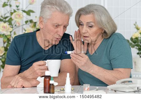 portrait of  senior couple with pills at home
