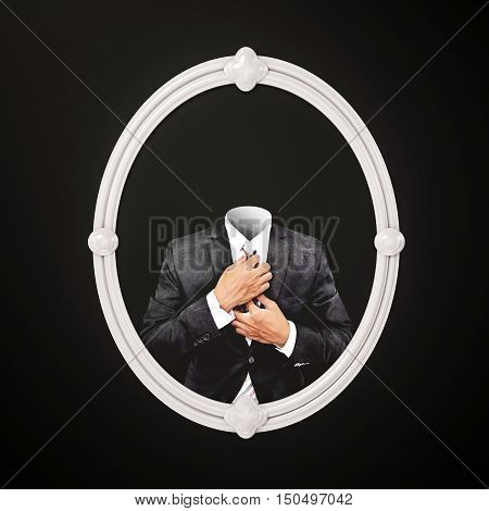 Invisible man in black suit, in white oval picture frame on black wall