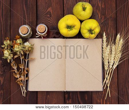 Kitchen book with blank pages to write text on the wooden background with quince and wheat spikelets. Copy space. Food background. Autumn harvest. Open notebook with blank pages on wooden background.