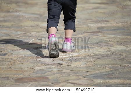 Unrecognizable Kid Walking Away On Stone Path