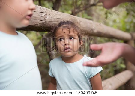 Portrait of innocent cute little girl looking at her sister and mother with eyes full of fear in park against trees