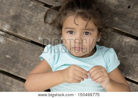 Top view of cute little girl with curly hair looking at camera with unhappy face over wooden ground.