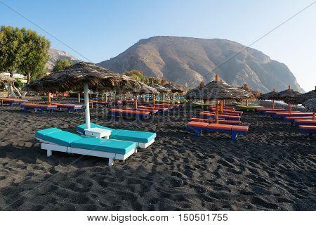 Tanning beds and umbrellas on Perissa beach Santorini Greece