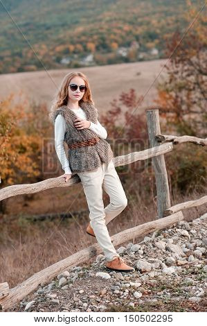 Stylish teen girl 13-14 year old posing at country side in modern clothes outdoors. Looking at camera. Childhood.