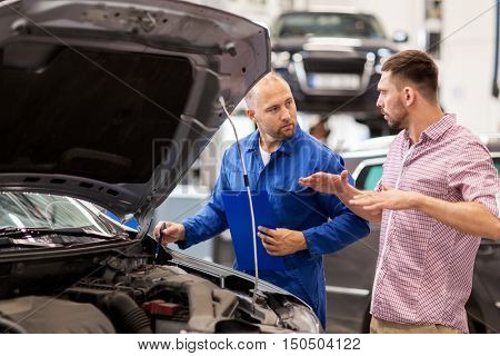 auto service, repair, maintenance and people concept - mechanic with clipboard and man or owner talking at car shop