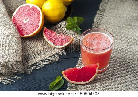 Glass of freshly squeezed grapefruit juice on wooden table. Drink for dieting. Focus on glass.