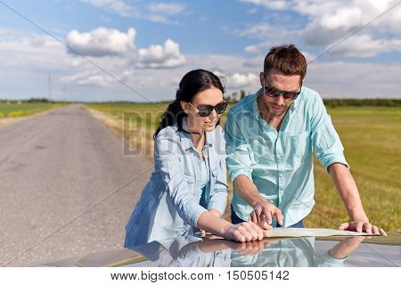 road trip, travel, tourism, family and people concept - happy man and woman searching location on map on car hood outdoors
