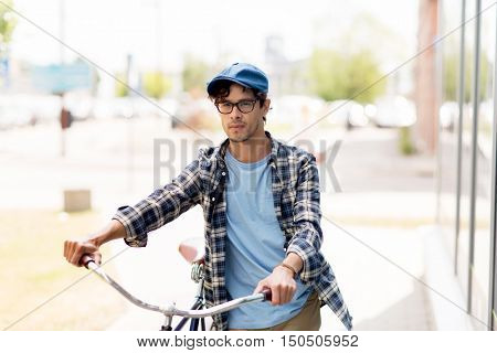 people, style, city life and lifestyle - young hipster man in vintage cap and fixed gear bicycle walking along city on street