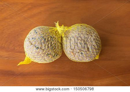 Suet treats, bird food in  meshed bag full of nuts sunflower seeds grains fat for birds to eat during winter, on wooden background