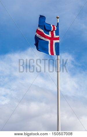 The national flag of Iceland waving on a flagpole against a blue cloudy sky
