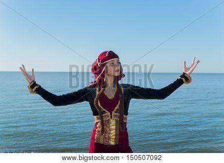 young woman dancing georgian national clothes sea outdoors summer sunny