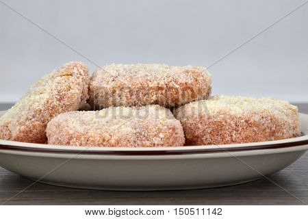 The raw meatballs made from minced meat on a plate before frying. White background. Patties.