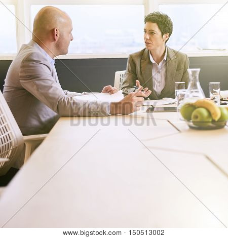 Square image of business man and woman seated at conference table early in the morning conducting a meeting in a professional manner.