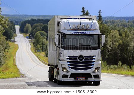 IKAALINEN, FINLAND - AUGUST 11, 2016: White Mercedes-Benz Actros refrigerated transport truck of Jarvimaki moves uphill on scenic road in South of Finland.