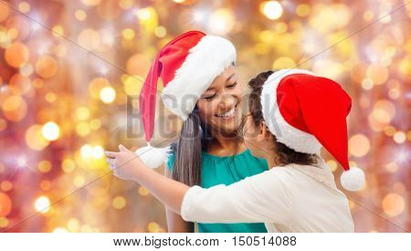 christmas, family, childhood and people concept - happy little girl in santa hat hugging her mother over holidays lights background