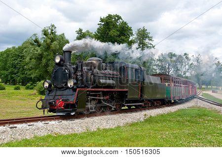old steam narrow-gauge railway locomotive in motion