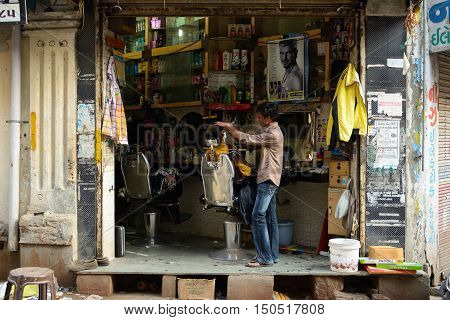 JUNAGADH GUJARAT INDIA - JANUARY 18: Man shaving off second at the makeshift hairdressing unit on one of streets in India in the Junagadh city in the Gujarat state in India Junagadh in January 18 2015