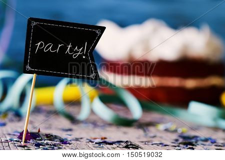 closeup of a black flag-shaped signboard with the word party written in it surrounded by streamers and confetti of different colors, and a cake in the background