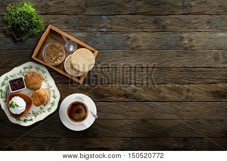 Scones with coffee and sour cream on wood background. View from above.
