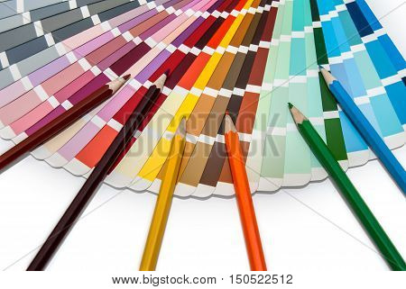 Color swatches book with color pencils on white background