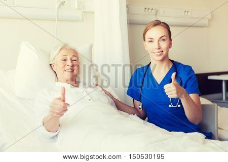 medicine, age, gesture, health care and people concept - doctor or nurse visiting senior woman and showing thumbs up at hospital ward