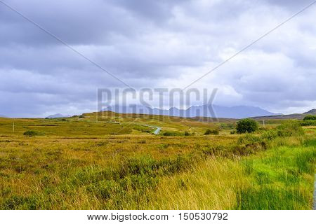 Beautiful barren landscape of Isle of Skye Scotland with winding narrow road running through it and peaks of Cuillin mountain range reaching into the clouds on the horizon