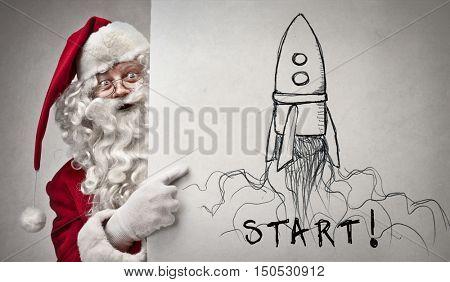 Santa Claus pointing at a rocket