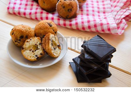 Cut little chocolate muffins on white plate with crushed chocolate on wooden background