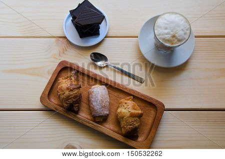 Beautiful breakfast. Glass cup of coffee with milk served with crushed chocolate on the plate and three different pastries on the wooden try.