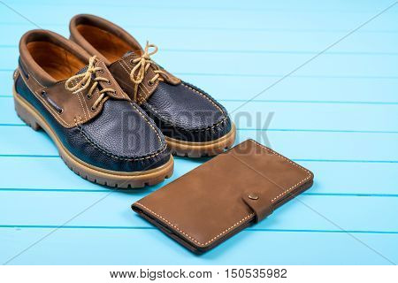 Men's accessories with a brown purse and shoes. Top view on wooden background.