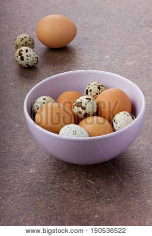 Chicken and quail eggs by Easter in the lilac ceramic bowl on a brown surface.