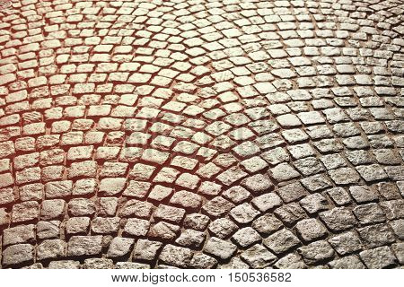 Perfect cobblestone streets of the city. Paving stone roadbed made with small stone blocks. Vintage tone.