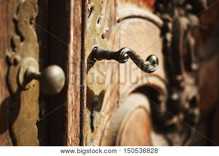 Beautiful old metal handle on an antique wooden door.