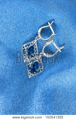 Sapphire earrings on blue cloth as a background