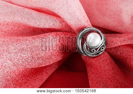 Vintage pearl ring on draped red cloth as a background