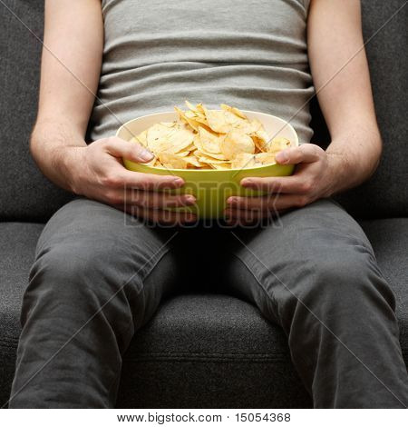 A man on a couch eating potato chips