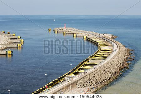 KOLOBRZEG POLAND - JUNE 22 2016: Breakwater built of concrete together with steel structure painted in yellow color protects the waterway to the sea port from the action of the waves