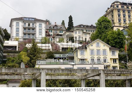 LUCERNE SWITZERLAND - MAY 03 2016: City buildings rise up on the slope. Vegetation among architecture shows the tourist attractive nature of the city