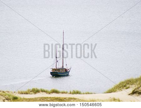 Ship under sail with the shore in the background