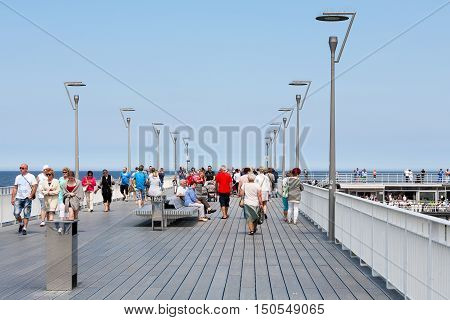 KOLOBRZEG POLAND - JUNE 19 2016: Unidentified vacationers strolls on the pier built over the Baltic Sea waters its contemporary version can be seen after general overhaul that was done in 2014
