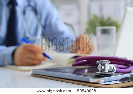 Male doctor using a laptop sitting at his desk .