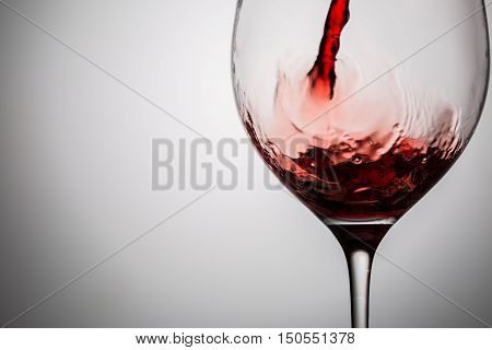 Pouring red wine into transparent glass. Image with copy space