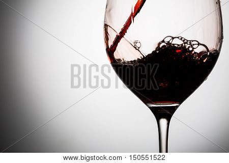 In beautifull glass poured red wine with waves and splashes, image on a light gray background