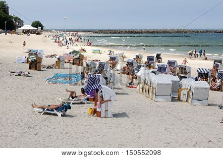 KOLOBRZEG POLAND - JUNE 19 2016: Roofed beach chairs in use by vacationers. Unidentified vacationers are relaxing and sunbathing on the shore of the Baltic Sea