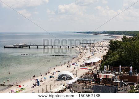 KOLOBRZEG POLAND - JUNE 22 2016: The coastline of the Baltic Sea. The pier over the Baltic Sea waters and many breakwaters were placed that protect the beach against effects of sea waves can be seen