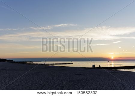 KOLOBRZEG POLAND - JUNE 27 2016: Just a few unidentified vacationers at dusk at the Baltic Sea beach enjoy their spare time during sunset
